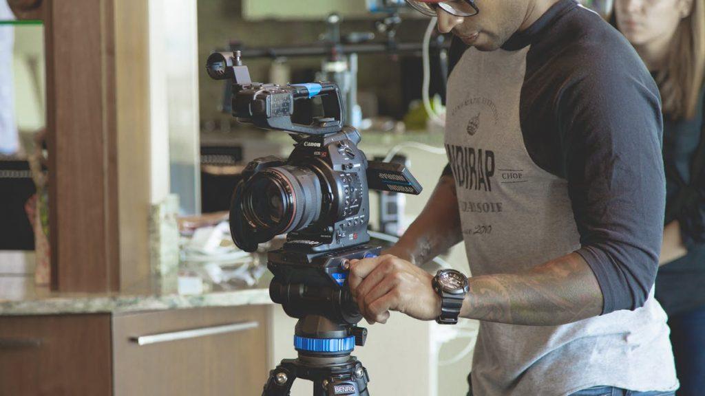 Un señor está grabando una escena con su cámara montada en un trípode