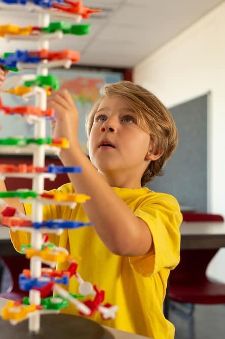 Vista frontal del modelo de Ciencia del niño caucásico aprendiendo en el aula de la escuela primaria