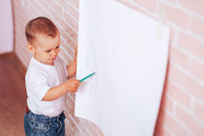 Little boy draws on paper
